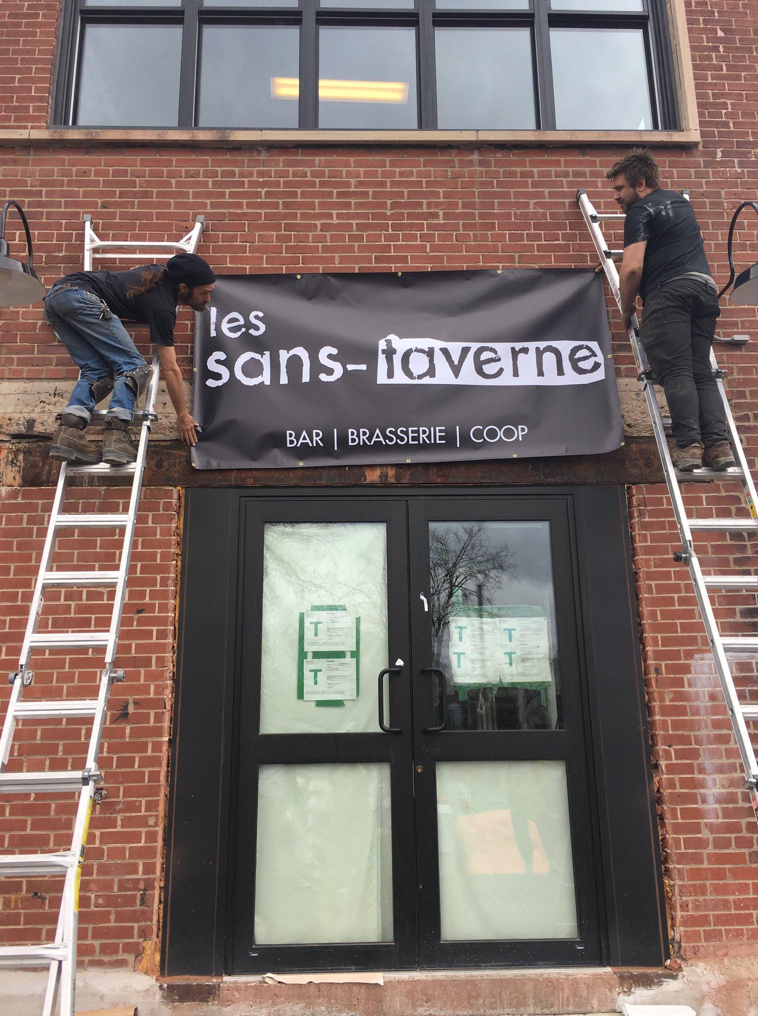 Deux hommes posent une bannière: Les sans-taverne